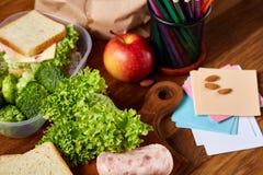Almuerzo sabroso con lechuga y verduras verdes en fuentes del envase y de escuela, en el escritorio de madera, foco selectivo Fotografía de archivo
