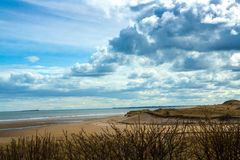 The coast at Alnmouth harbour at low tide. Alnmouth harbour and the estuary of the river Aln, in Northumberland, England, at low tide, where it flows into the stock images