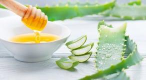 Aloés Vera com o close up do mel no fundo de madeira branco Cosméticos orgânicos naturais cortados da renovação de Aloevera, medi imagem de stock