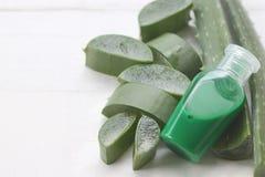 Aloe Βέρα φετών και πράσινο πήκτωμα μπουκαλιών που τοποθετείται σε ένα λευκό ξύλινο στοκ εικόνα με δικαίωμα ελεύθερης χρήσης