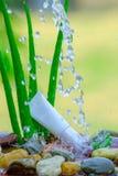 Aloe crema bianco vera del tubo sulle rocce con la spruzzatura dell'acqua Immagini Stock