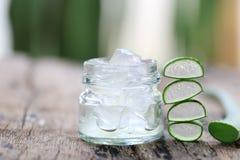 Aloe fresco vera e gelatina in bottiglia di vetro disposta su un flo di legno Fotografia Stock