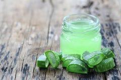 Aloe fresco vera e gelatina in bottiglia di vetro disposta su un flo di legno Immagine Stock Libera da Diritti