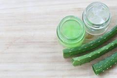 Aloe fresco vera e gelatina in bottiglia di vetro disposta su un flo di legno Immagine Stock
