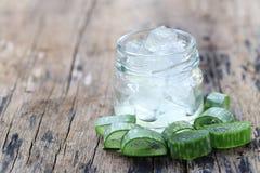 Aloe fresco vera e gelatina in bottiglia di vetro disposta su un flo di legno Immagini Stock