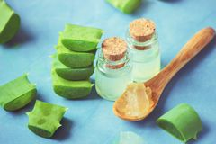 Aloe Vera extract in a small bottle and pieces on the table. Selective focus royalty free stock image