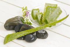 Aloe Vera Herbal e fetta di Vera dell'aloe con roccia nera su fondo bianco di legno Vista superiore e fine su Fotografia Stock Libera da Diritti