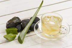 Aloe Vera Herbal e succo e fetta di Vera dell'aloe sul piatto con roccia nera su fondo bianco di legno Vista superiore e fine su Fotografia Stock Libera da Diritti