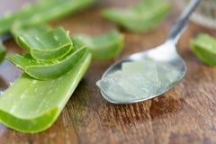 Aloe vera stelnar på skeden med aloe vera på trätabellen Arkivfoto