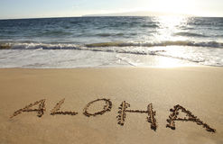 Aloha. The word Aloha written in a sandy beach Stock Photos