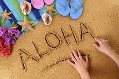 Aloha Hawaii beach word writing. Child writing the word Aloha on a sandy beach, with flowers, beach towel, starfish and flip flops Stock Photography