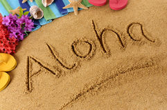 Aloha Hawaii beach. The word Aloha written on a sandy beach, with flowers, beach towel, starfish and flip flops Stock Images