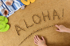 Aloha Hawaii beach. Aloha written in sand with towel, seashells and flip flops Stock Photos