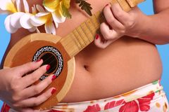 Aloha Belly. Close-up of a woman playing ukulele stock image