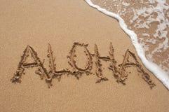 Aloha escrito na areia na praia com onda Imagens de Stock Royalty Free