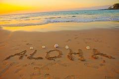 Aloha geschrieben in den Sand Stockbild