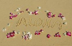 Aloha geschrieben in den Sand mit Orchideen in Hawaii Stockbild