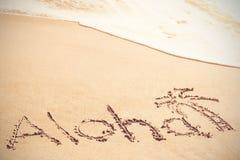 Aloha testo scritto sulla sabbia con la palma Fotografia Stock