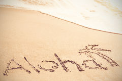 Aloha text written on sand with palm tree Stock Photography