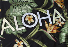 Aloha on Textile. The word Aloha on Textile with palm fronds, bird of paradise, leaves, and flowers Royalty Free Stock Photo