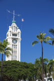 The Aloha Tower rising above palm trees Stock Photo