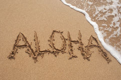 Aloha Written in Sand on Beach with Wave. Close up of the Hawaiian word Aloha written in the sand on the beach in Hawaii with a wave breaking in the top right Royalty Free Stock Images