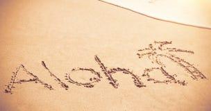 Aloha written text with palm tree on sand Stock Photos