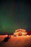 Alojamento iluminado sob as luzes do norte Imagens de Stock Royalty Free