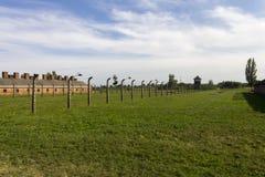 Alojamiento barato para los presos de Auschwitz, la cerca del alambre de púas y una torre de guardia Imágenes de archivo libres de regalías