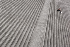 Alone. Young man sitting alone on a huge flight of steps outside the Paris Bibiliotheque Stock Image