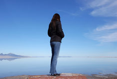 Alone. Woman standing alone in front of a lake Stock Image