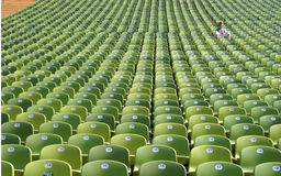 Alone. One single person in a football stadium Stock Photo