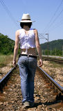 Alone. Girl going on the rail tracks Royalty Free Stock Images
