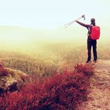 Alone adult backpacker with poles in the air,  open view on mountain valley, misty rainy day Royalty Free Stock Image