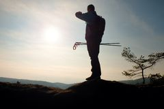 Alone adult man backpacker at sunrise at open view on mountain peak Stock Images