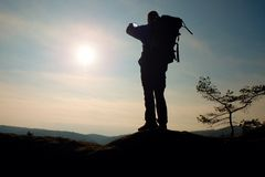 Alone adult man backpacker at sunrise at open view on mountain peak Stock Photos