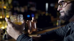 Alone adult man is drinking beer sitting in a bar in evening time, tasting cocktails, rotating glass on a counter. Drink and beverage stock video