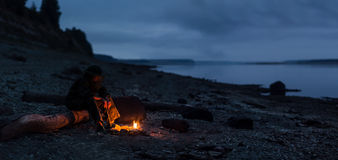 Alone ady hiker sitting by the bonfire at river shore. Focus on fire and feet. Royalty Free Stock Photography