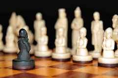 Alone against the enemy .. A brave pawn facing the white enemy on a chessboard Royalty Free Stock Image