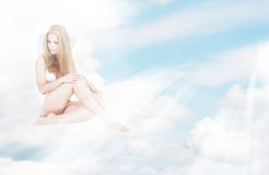 Alone angel girl in sun rays on clouds Stock Image