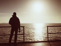 Alone artist on wooden sea bridge.  Man on wooden sea mole Stock Photo