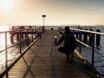 Alone artist on wooden sea bridge.  Man on wooden sea mole Stock Images