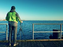 Alone artist on wooden sea bridge.  Man on wooden sea mole. Alone artist on wooden sea bridge. Photographer with with mirror camera and tripod at end of pier Stock Images