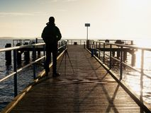 Alone artist on wooden sea bridge.  Man on wooden sea mole. Alone artist on wooden sea bridge. Photographer with with mirror camera and tripod at end of pier Royalty Free Stock Images
