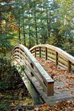 Alone on an Autumn Afternoon. Scenic wooden bridge is deserted except for the leaves that litter the rustic boards Royalty Free Stock Image