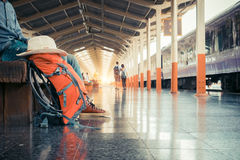 Alone backpacker and hat at the train station with a traveler an Royalty Free Stock Image