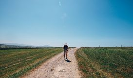 Alone backpacker traveler walks on contryside road in sultry aft. Ernoon Royalty Free Stock Photo