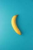 Alone banana. Banana on sky blue paper background with space Stock Image