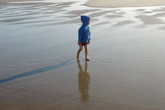 Alone at the beach. Little boy looks back standing on a cold wet sand at Long Beach, Washington Stock Photos