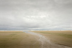Alone on Beach. In the distance a young woman walks through a secluded beach on a rainy day Royalty Free Stock Photos